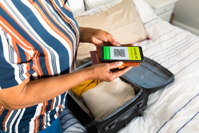 Midsection of senior african american woman holding smartphone with covid vaccine passport