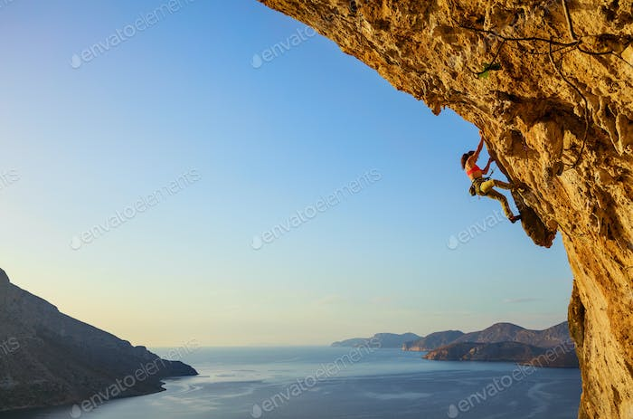 Young woman climbing challenging route at sunset