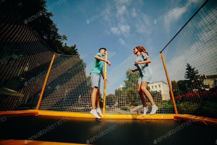 Paar springen auf Trampolin im Park