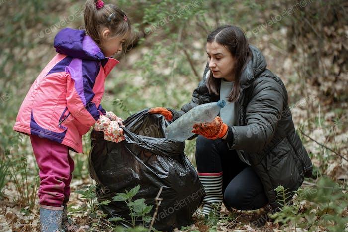 Mama und Tochter räumen Müll im Wald auf.
