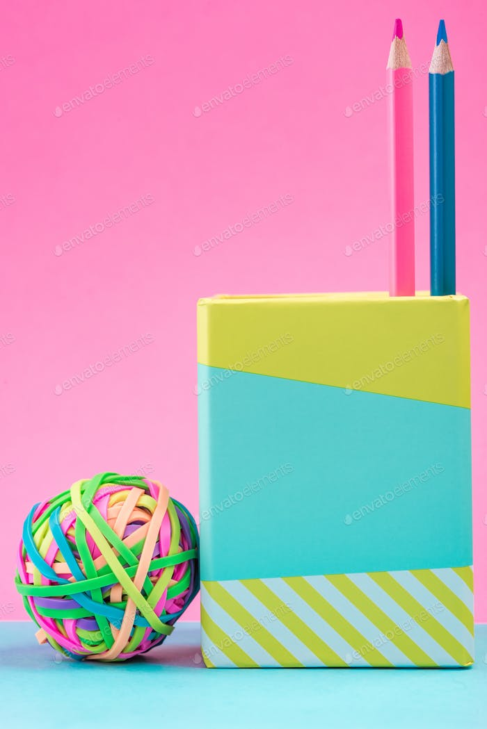 Office Supplies and Rubber Band Ball on Pink Pastel Background