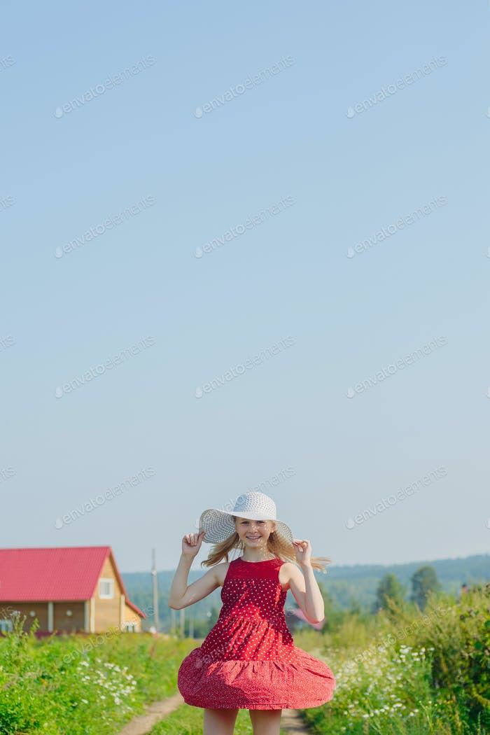 Little girl in red dress and white hat with large brim