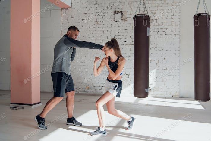 Das erste Training eines unerfahrenen Mädchen-Kämpfers im Kickboxen, zeigt der Trainer die Schläge