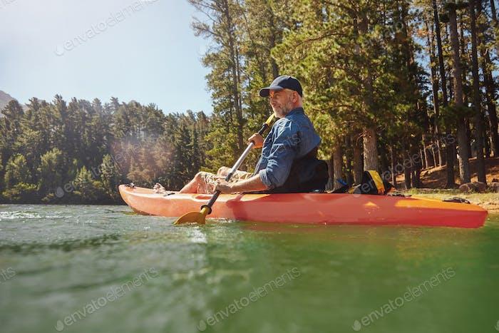 Reifer Mann mit Kajak in einem See