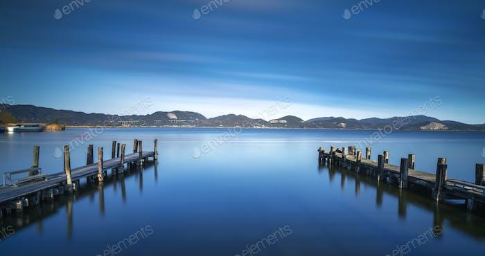 Zwei hölzerne Pier oder Steg auf einem blauen See. Versilia Toskana, Italien
