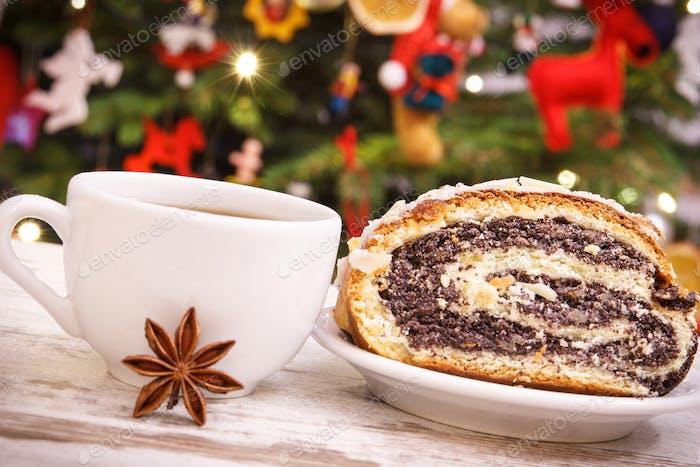 Frischer polnischer Mohnkuchen, Kaffee oder Tee und Weihnachtsbaum mit Beleuchtung und Dekoration