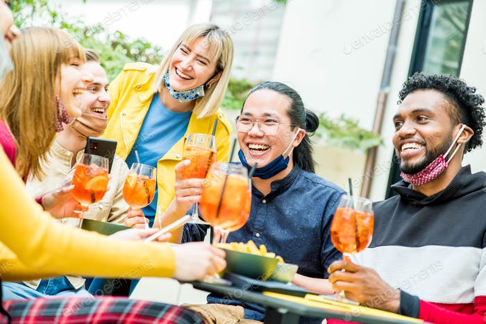 Multiracial friends wearing face masks drinking cocktails at rooftop party