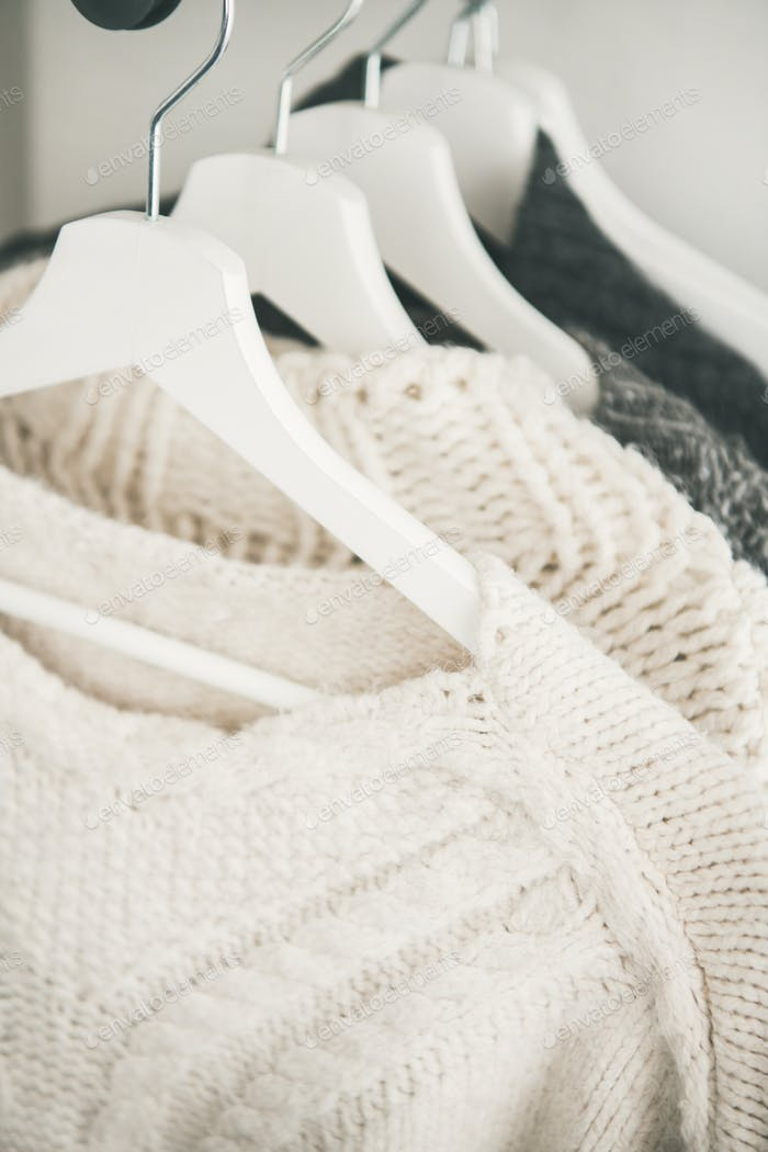 Row of warm knitted sweaters hanging on hangers, selective focus