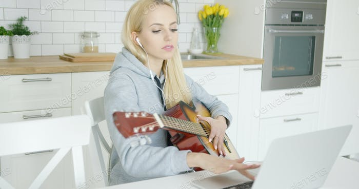 Girl practicing guitar and using laptop
