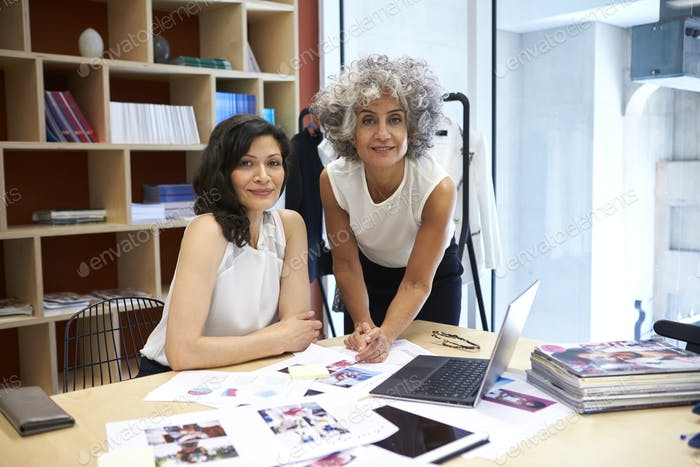 Two female creatives working in office looking to camera