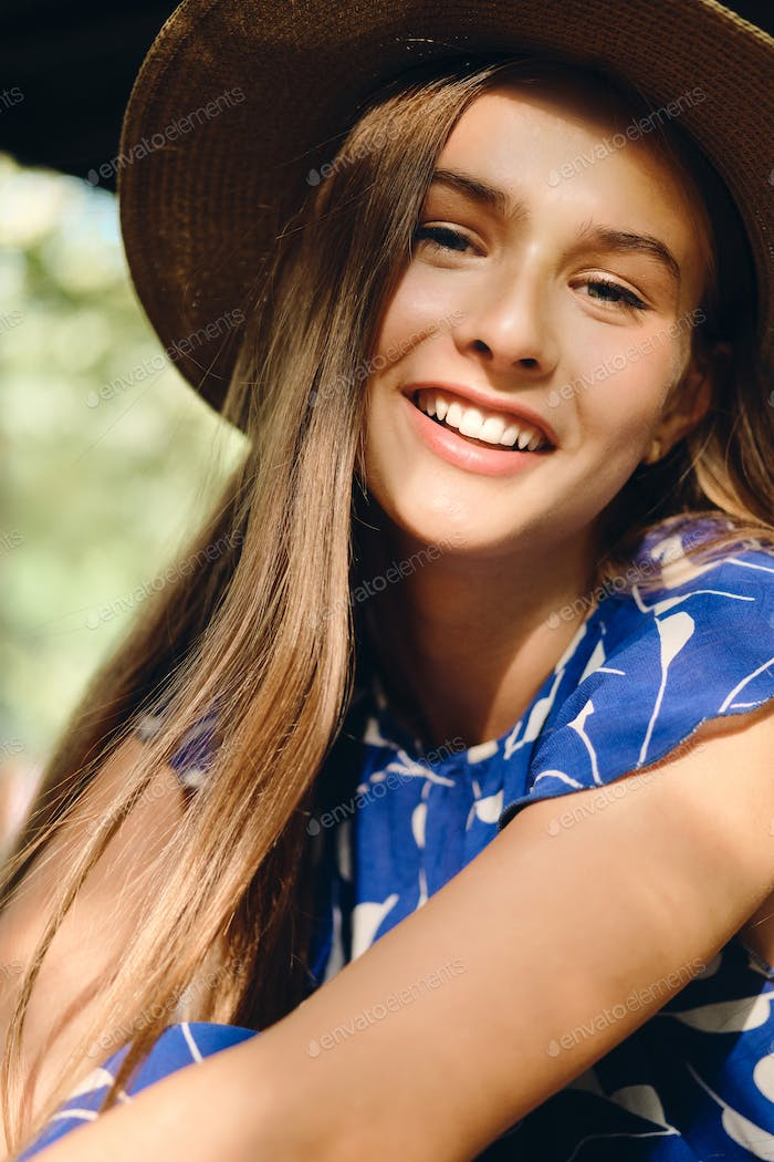Portrait of pretty smiling girl in blue dress and hat happily looking in camera sitting in city park