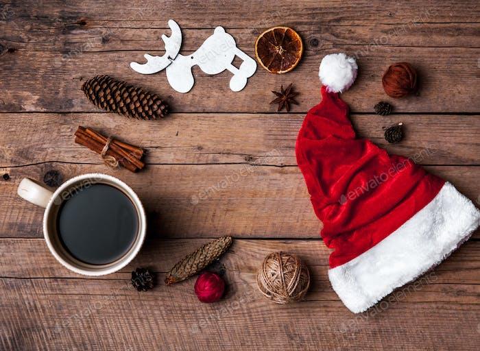 Cup of coffee and Santas hat, Christmas set, gift and Christmas tree. Celebration