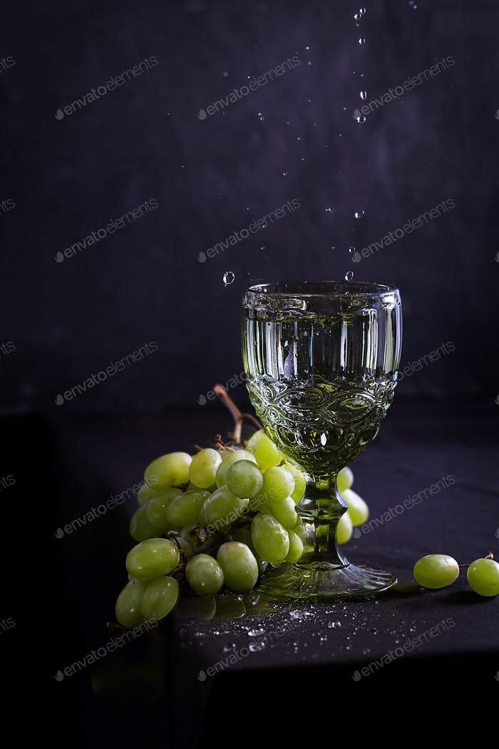 Still life with wine, grapes and old style glass