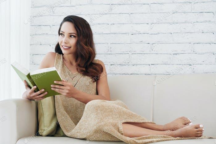 Attraktive Dame träumt beim Lesen Romantik Buch