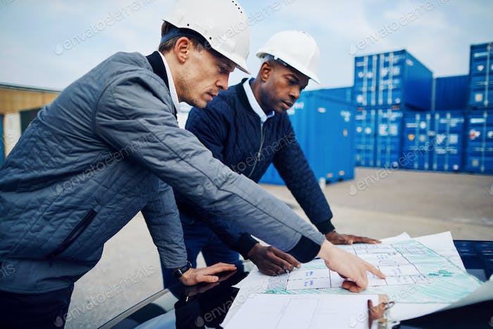 Engineers discussing plans while working in a commercial shipping yard