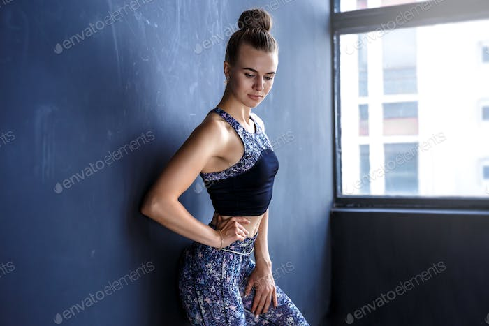 Beautiful fitness model is posing in front of the dark wall in a dark training suit
