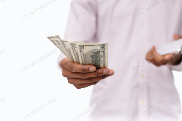 Unrecognizable black man holding bunch of dollars and smartphone