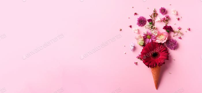 Summer minimal concept. Ice cream cone with pink flowers and leaves on punchy pastel background