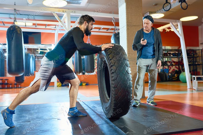 Sportsman flipping huge tyre in gym