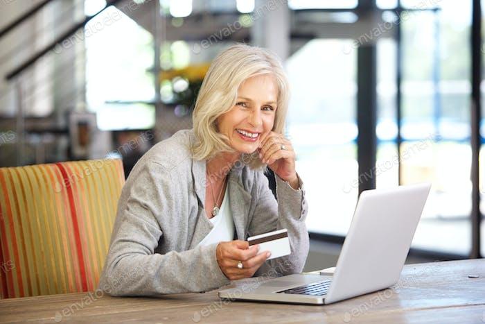 schöne ältere Frau mit Laptop-Computer und Kreditkarte