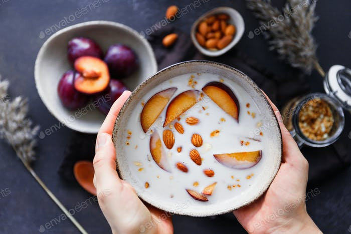 Hands hold a bowl of morning porridge with almond and sliced plum.