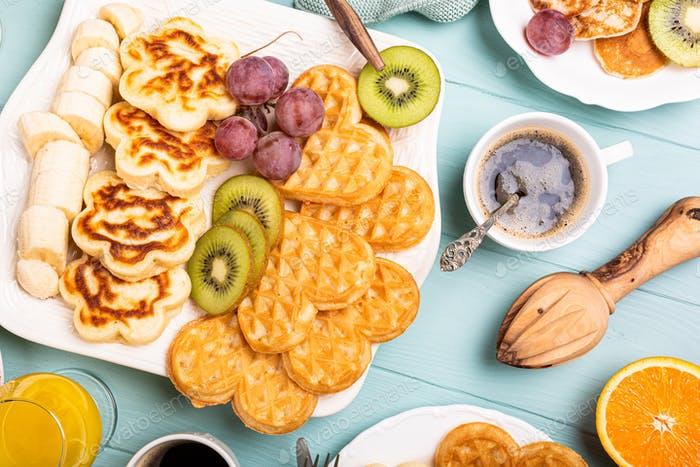 Healthy breakfast with fresh hot waffles hearts, pancakes flowers
