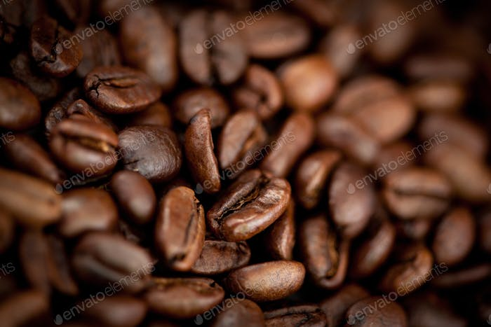 Close up of dark blurred coffee seeds laid out together