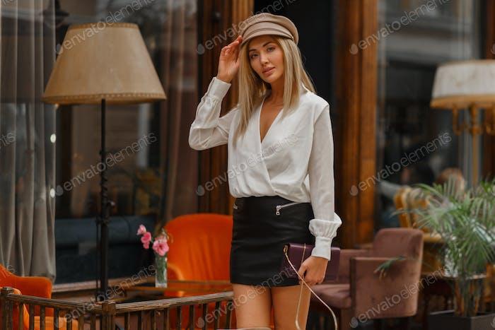 Blond model  posing   near cafe.