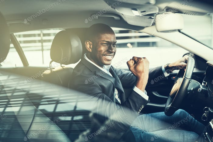 Smiling African businessman fist pumping while driving in his car