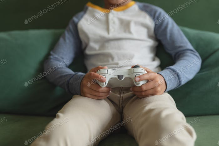Mid section of Caucasian boy playing video game in living room at home
