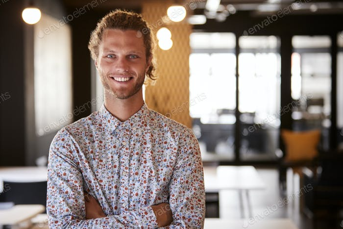 Millennial white male creative standing in an office with arms crossed, smiling to camera, waist up
