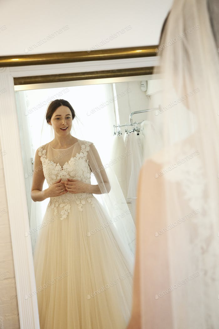 A woman in a wedding dress, standing in front of the mirror, in a bridal boutique.