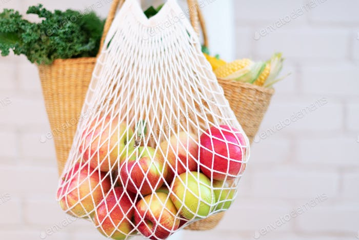Girl holding reusable mesh bag full of apples, straw basket with organic vegetables. Banner. Copy