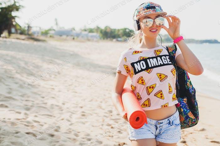 young beautiful woman walking on beach with yoga mat