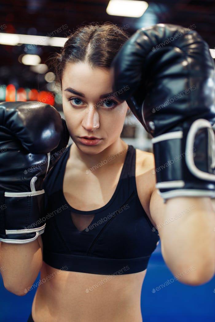 Woman in black boxing gloves, closeup front view