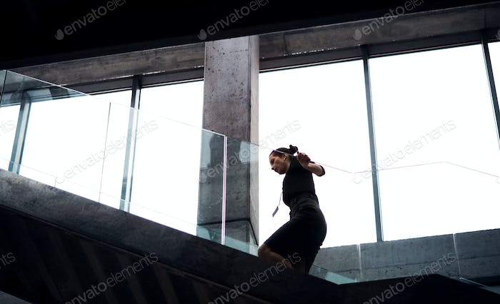A young businesswoman walking up the stairs in office building.