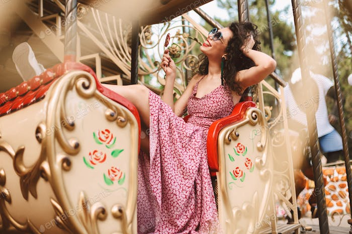 Pretty girl in sunglasses and dress holding lolly pop happily riding on carousel in amusement park
