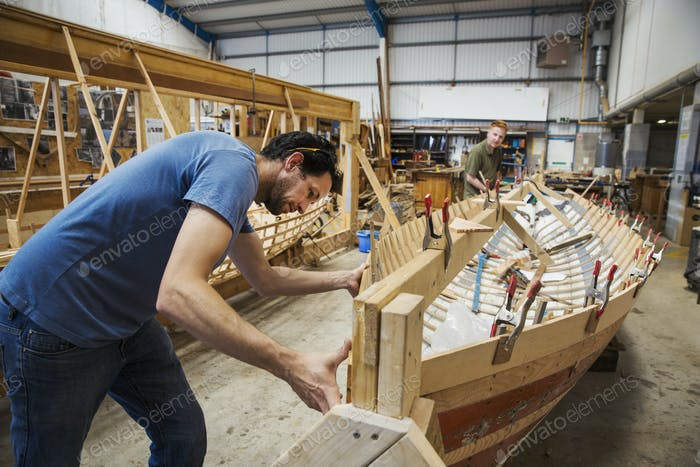 Two men in a boat-builder's workshop, working together on a wooden boat hull.