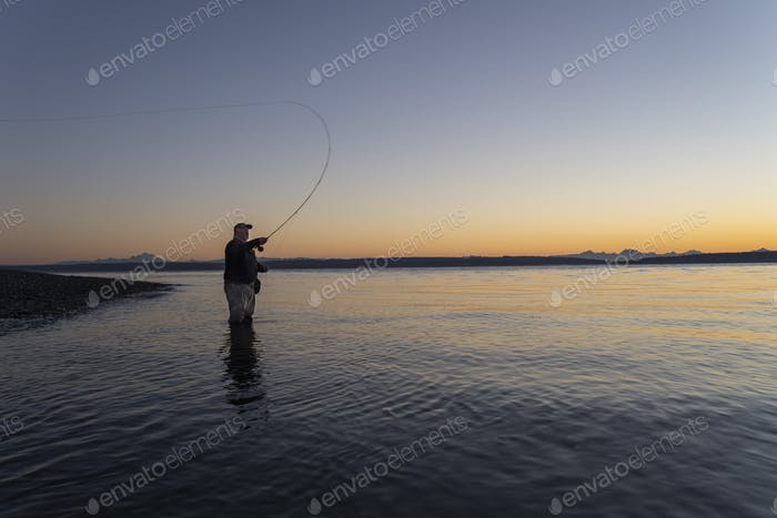 A silhouette view of a fly fisherman casting for salmon and searun coastal cutthroat trout from a
