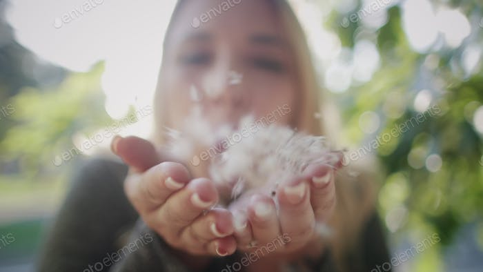 Pretty Blonde Girl Blow Away Plant Fluff Closeup