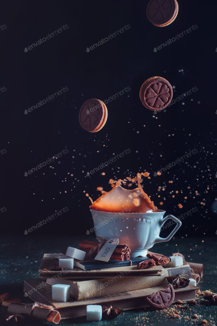 Porcelain tea cup with falling cookies and a splash on a dark background. Frozen motion food