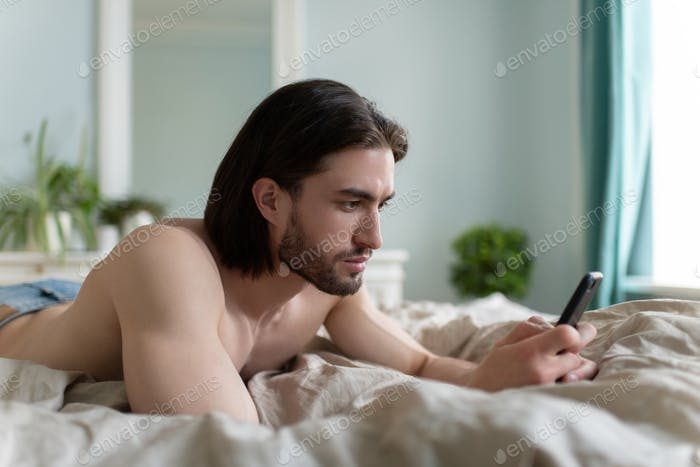 Man using his phone while he lying On Bed