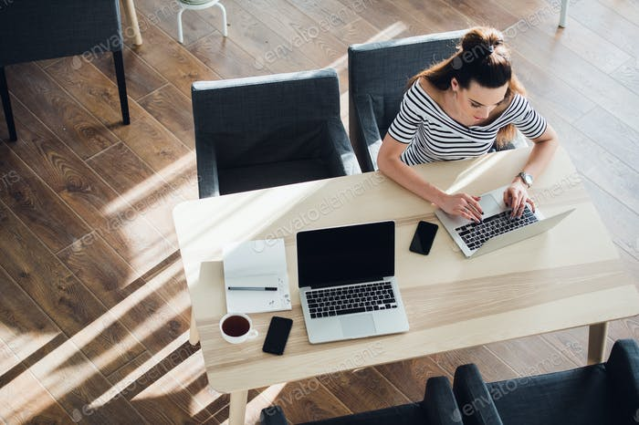Top view of an adult woman sitting at desk and working on her laptop, her table is perfectly tidy