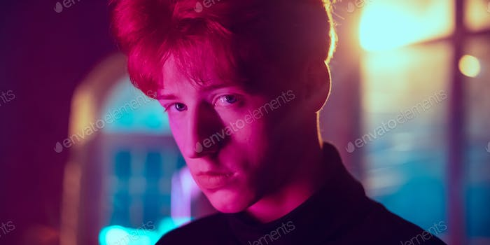 Cinematic portrait of handsome young man in neon lighted interior