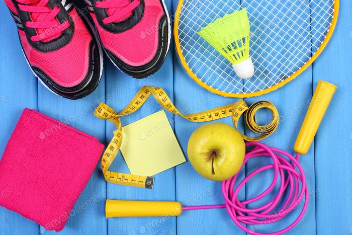 Pink sport shoes, fresh apple and accessories for sport on blue boards