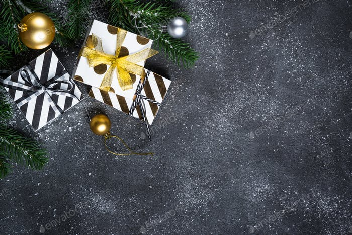 Christmas background - Gold and silver decorations and present box on black stone background