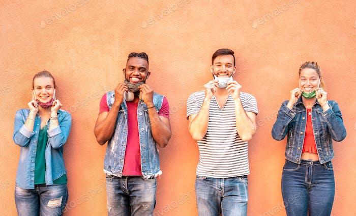 Multirassische Millennial-Freunde lächeln mit offener Gesichtsmaske