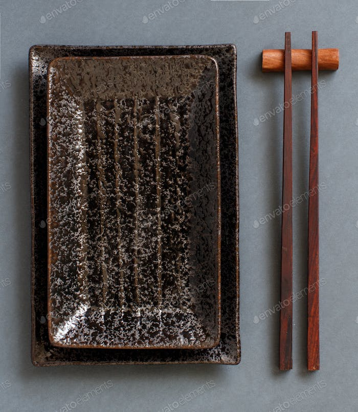 Chopsticks and rectangular plates on dark gray background top view