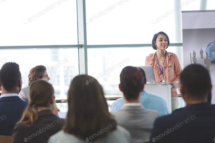 Front view of mixed-race female speaker with laptop speaks at a business seminar in office building