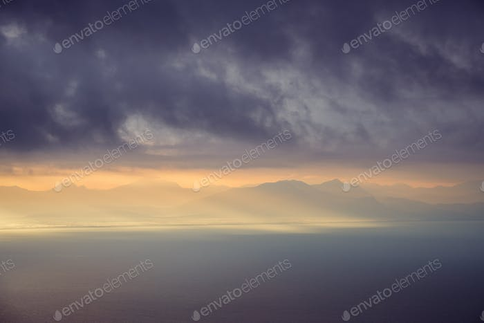 Dramatic landscape view of sunrise over mountains and the ocean